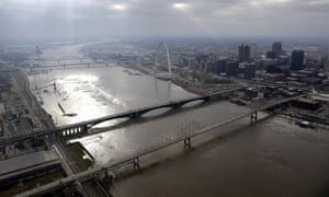 The swollen Mississippi River flows past the Gateway Arch in St Louis. Flood waters have begun to recede along the length of the Mississippi.