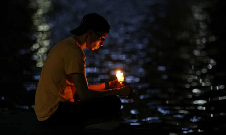 A man sits by Lake Enola as he takes part in a vigil for the Pulse night club victims.