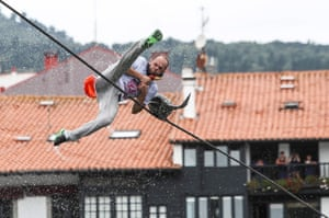 A participant falls into the water after picking up a false goose from a rope during the celebration of the traditional Goose Day contest in Lekeitio, Spain