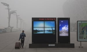 Screens show Beijing's Olympic Green park under blue skies amid heavy smog.