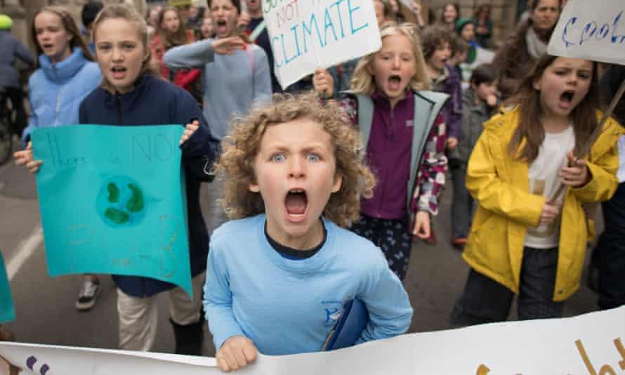 schoolchildren marching through Cambridge city centre during a climate change protest.