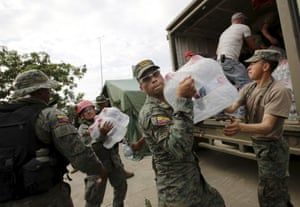 Soldiers carry water from a truck after an earthquake struck the town of Canoa