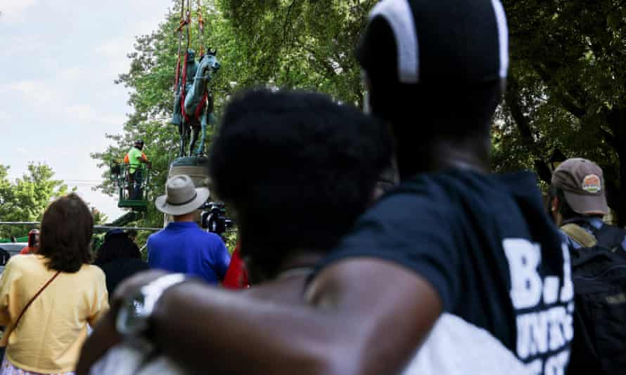 """People look on as workers prepare to remove a statue of Confederate General Thomas """"Stonewall"""" Jackson in Charlottesville, Virginia, on 10 July."""