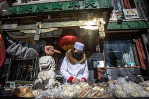 Beijing, China: A vendor wearing a protective mask packs food for customers on the street near the Houhai lake