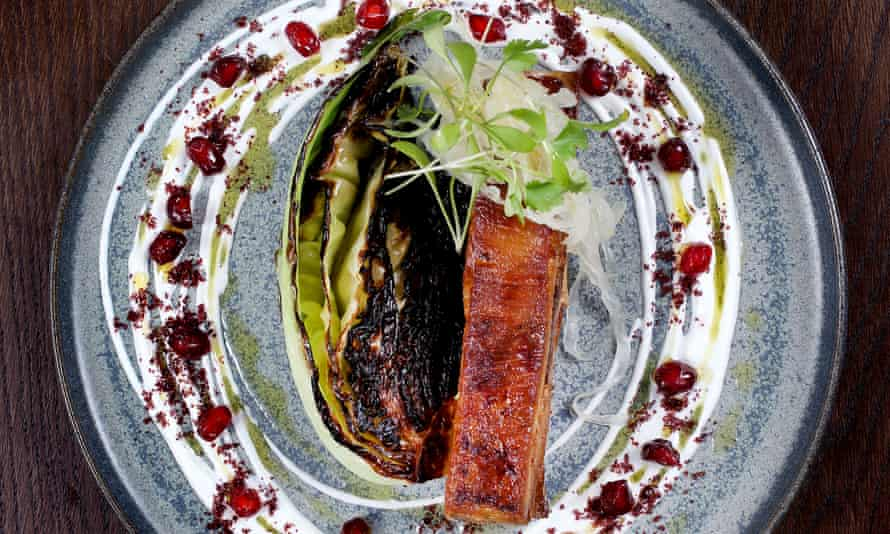 A piece of mahogany-coloured lamb belly, charred cabbage on the side, on a round plate edged with yogurt and pomegranate seeds