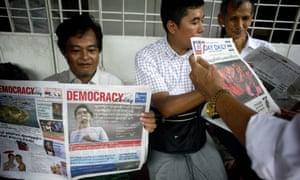 Supporters of Myanmar opposition leader Aung San Suu Kyi read the official results of the elections from a newspaper outside the National League of Democracy headquarters in Yangon