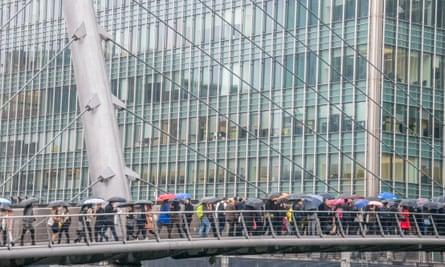 Commuters walking across a bridge in Canary Wharf, London.
