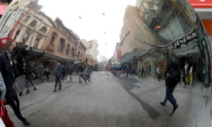 Pedestrians are seen in Rundle Mall in Adelaide reflected in a silver ball