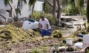 A man shovels seagrass from the entrance of his mobile home in the wake of Hurricane Irma at Tavernier Key, Florida.