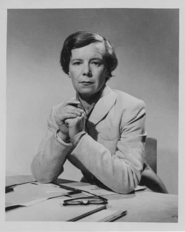 Alison Adburgham sits with her elbows on her desk and her hands clasped in front of her, looking directly at the camera, wearing a pale jacket buttoned up.