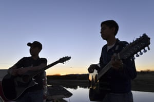 Two Mexican boys play guitars along the bank of Rio Bravo in Ojinaga