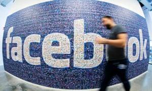 a Facebook employee walks past a Facebook sign