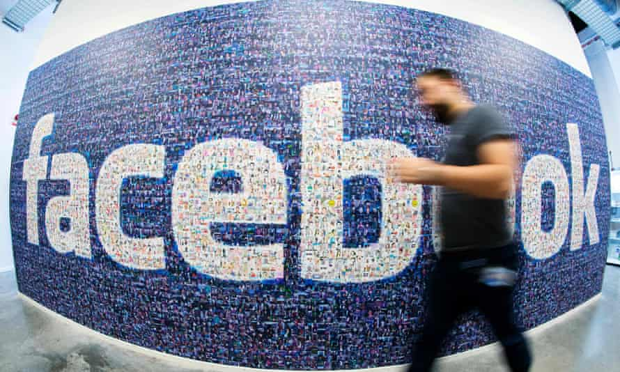 man with beard and work pass walking past a facebook logo on a wall taken with a fisheye lens