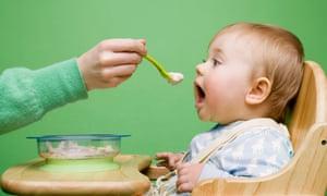 adult feeding a baby