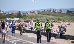Police walking along road next to beach in Troon, Scotland, on Sunday.