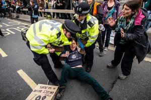 Police apprehend a protester on Waterloo Bridge