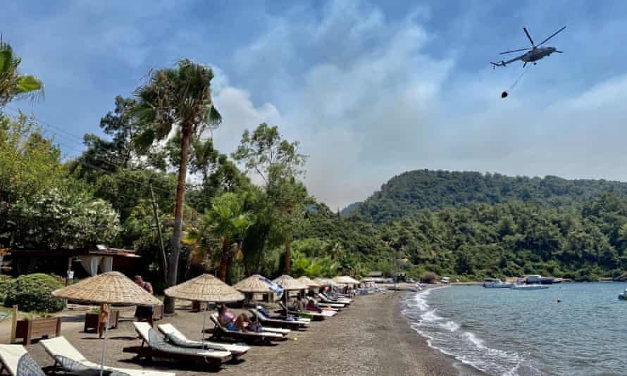 Sunbathers watch as a helicopter carries water from the sea to dump on fires near Marmaris.