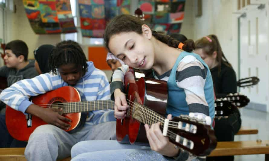 Pupils learn to play the guitar in a music lesson.