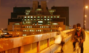 Two blurred people walk past the MI6 government intelligence service building, Vauxhall, London.