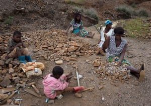 Women and children crush rocks to sell as gravel in Kabwe, Zambia