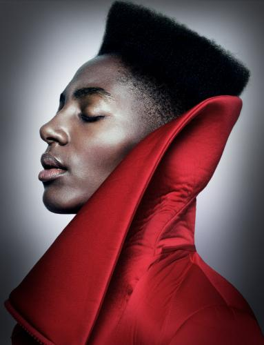 Head and shoulders of Ysra Daley-Ward in profile with her eyes closed wearing a red cloak with a large turned up collar