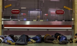 Refugees sleep on the ground next to closed ticket counters in Munich.