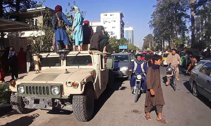 Taliban fighters stand on a vehicle along the roadside in Herat, after Afghan government forces pulled out of the city.