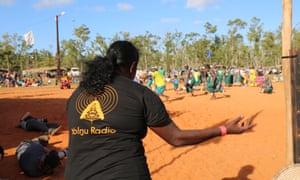 A woman wearing a Yolngu radio t-shirt at a festival