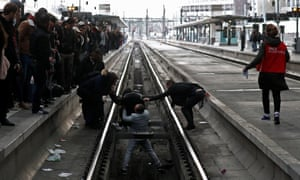 Commuters help a woman who fell on to railway tracks at the Gare de Lyon in Paris.