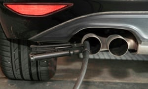 A hose for an emission test is fixed in the exhaust pipe of a Volkswagen Golf diesel car