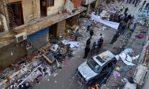 Police and Hezbollah members inspect the damage after a twin suicide attack in Beirut.