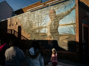 "Visitors look at a mural of Harriett Tubman called ""Take My Hand,"" painted by Michael Rosato, at The Harriet Tubman Museum & Educational Center."