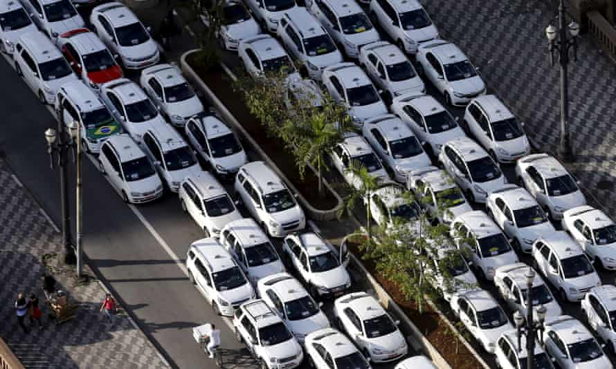 People pass taxis parked on the street during a protest against Uber in downtown São Paulo