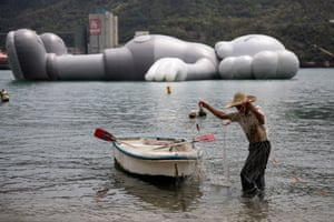 A fisherman in Hong Kong sorts his net next to the 37-metre-long inflatable sculpture KAWS:Holiday by the US artist Brian Donnelly