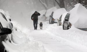 During winter storm Juno In the South End, Mike Poremba walks his dog Cali past snow-covered cars.