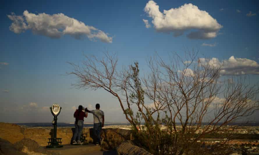 People look through binoculars towards the US-Mexico border separating El Paso and the Mexican city of Ciudad Juárez.