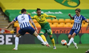The Canaries' Josip Drmic passes between the Seagulls'Leandro Trossard and Lewis Dunk.