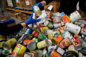George Washington University School of Medicine students sort canned and other non-perishable food as they wear disposable gloves at Capital Area Food Bank in Washington, Thursday, March 19, 2020.