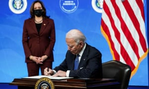 Joe Biden signs an executive order after speaking about his administration's plans to strengthen American manufacturing as Vice President Kamala Harris listens in the South Court Auditorium at the White House, moments ago.