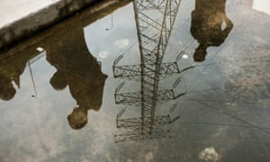 An electricity pylon is reflected in a puddle in Kaleta, Guinea