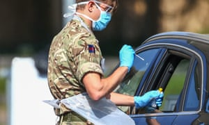 A member of the military takes a swab from a person at a drive-in Covid-19 testing centre at Chessington World of Adventures