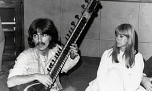George Harrison playing a sitar in India in 1968 with British actor Rita Tushingham.