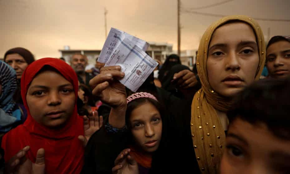 A displaced woman shows her refugee identification paper in Qayyara, south of Mosul, Iraq.