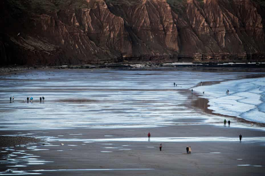 People take a walk along the beach, with Filey Brigg in the background.