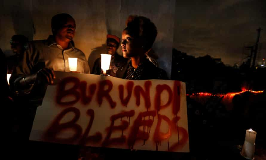A woman holds a placard reading 'Burundi bleeds' during a candlelight vigil calling for peace in the country held last December in the Kenyan capital Nairobi