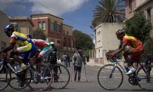 Cyclists during a street race in front of a villa influenced by Italian avant-garde architecture in Asmara.