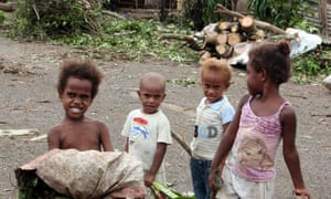 Children stand in front of debris on a street near their homes after cyclone Pam hit Port Vila.