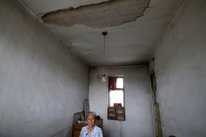 Gao Xiuzhen, 81, stands inside her damaged house in an area where land is sinking next to a coal mine, in Shiyanzhuang village of Datong.