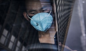 A man in a protective mask waits in a car in Beijing's central business district