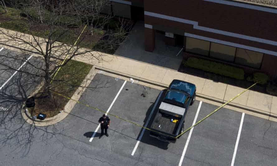 An official stands near a taped-off area near the scene of a shooting at a business park in Frederick, Maryland.